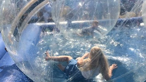 entertainment for children in an amusement park - a girl in a large inflatable balloon