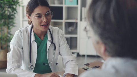 Female doctor giving an handshake to her patient