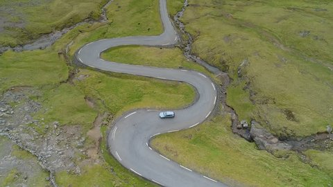 AERIAL: Flying above a car on scenic cruise down an empty rural asphalt road running through the beautiful mainland of picturesque Faroe Islands. Car driving through the sharp turns of a country road.