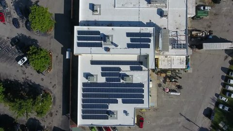 Aerial top down view of newly built apartment complex with photovoltaic solar panels installed they absorb sunlight as source of energy to generate electricity in this residential applicatio