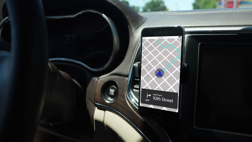 A smartphone attached to the dash on a vent holder in a moving car shows a ride sharing app with route in progress. App screen simulated.	 	 | Shutterstock HD Video #1015169206