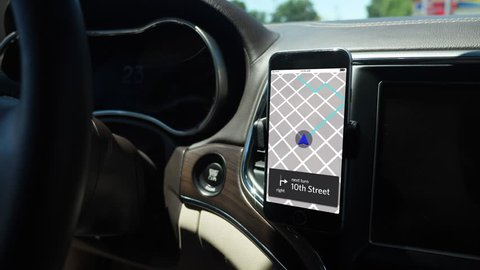 A smartphone attached to the dash on a vent holder in a moving car shows a ride sharing app with route in progress. App screen simulated.