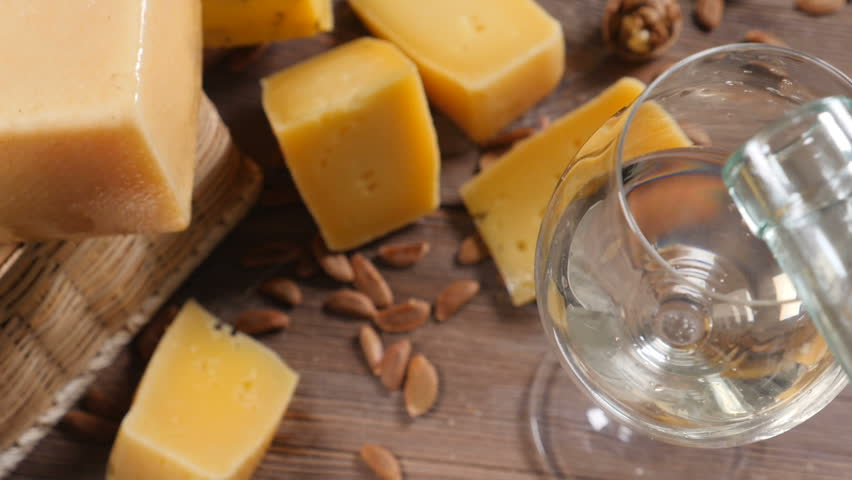 Wine and cheese. Food art. Different sorts of hard cheese beautifully surved on a wooden background. White wine is being poured into wine glass.
