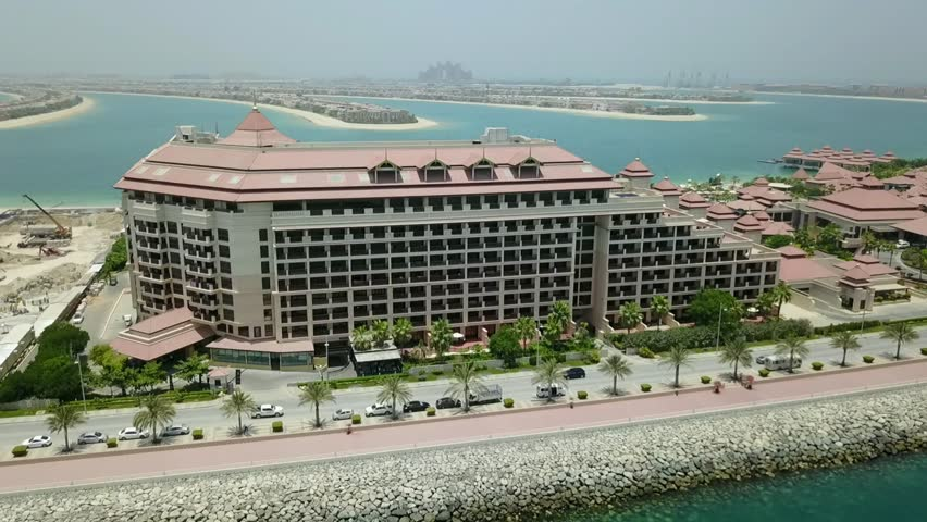 A high pass of Dubai Palm Island, Palm Jumeirah and the Anantara hotel complex from above the Persian gulf, following the frontage of the outer ring of the island and looking over to the palm fronds