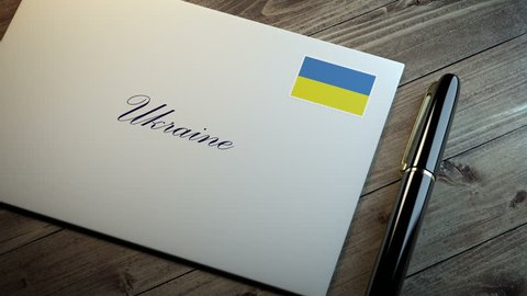 Country name written on a card or envelope in cursive font with a sleek pen on a wooden table surface under beautiful classy light. Stamp in the corner shows the flag of Ukraine