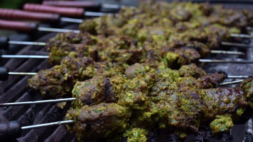 Closeup of beef shish kabobs on grill at low angle showing the kabobs in a nice arc.