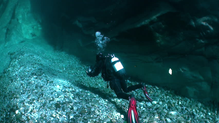 Camera operator diver underwater in transparent river Verzasca. Shooting a frame of picturesque nature on background of huge smooth stones. | Shutterstock HD Video #1015244086