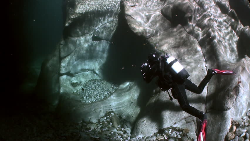 Camera operator diver underwater in transparent river Verzasca. Shooting a frame of picturesque nature on background of huge smooth stones. | Shutterstock HD Video #1015244206