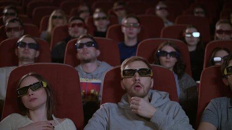 Spectators in 3d glasses watching film in cinema. People watching film at movie theatre. 3d movie audience. People in 3d glasses at movie hall in slow motion