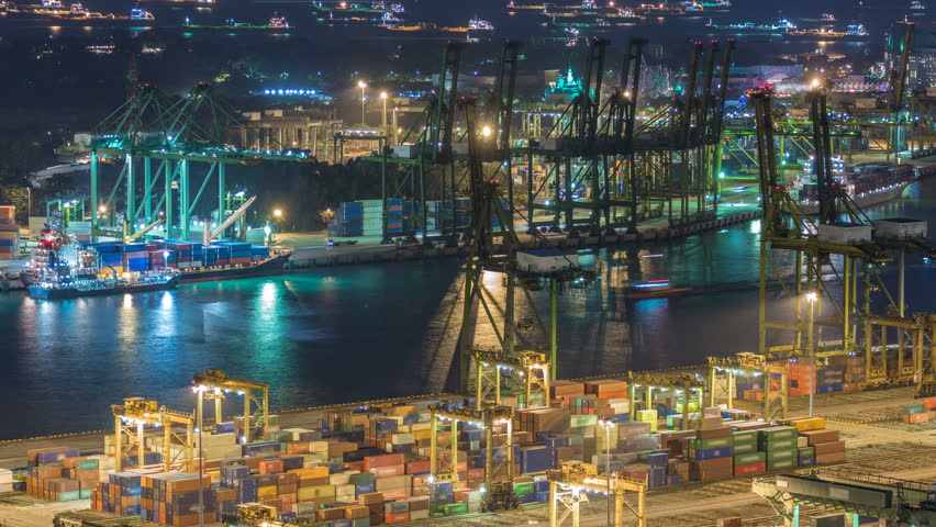 Commercial port of Singapore night timelapse. Bird eye panoramic aerial view of busiest Asian cargo port with hundreds of ships loading export and import goods and thousands of containers in harbor