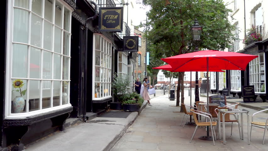 LONDON, ENGLAND, AUGUST 18TH, 2018: Woman shopkeeper and customer on Woburn Walk, which in 1822 was London's first pedestrian street, featuring Dickensian bow fronted buildings. Slow motion | Shutterstock HD Video #1015299226