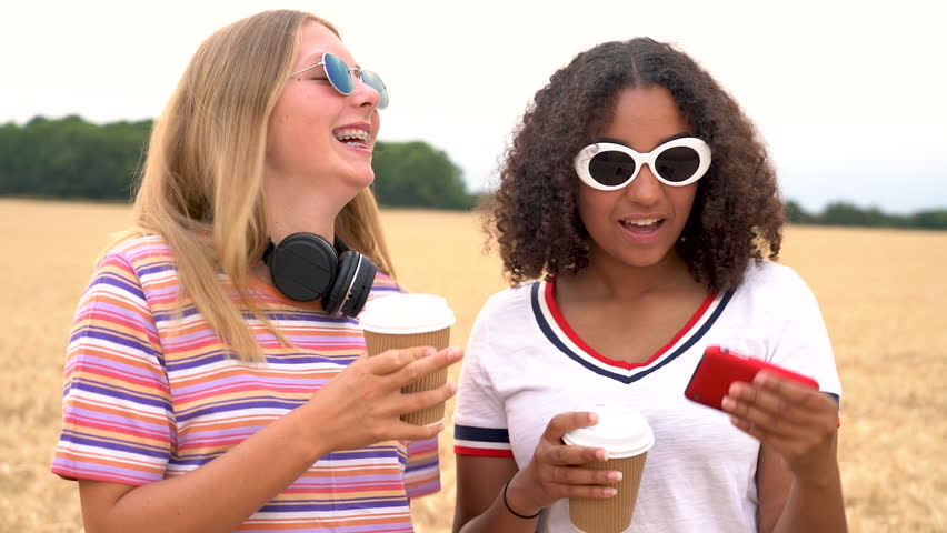 Slow motion video clip of pretty blonde girl and mixed race teenager young women wearing sunglasses drinking coffee and taking selfies on their smart phones