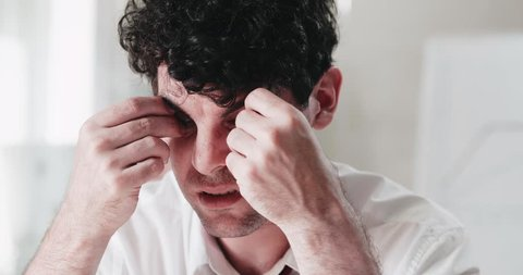 Close-up of extremely tired man putting matches into his eyes