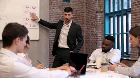 Young Attractive Businessman Standing near Whiteboard. Pointing on Papers with Graphs and Charts. Explaining his New Project to his Young Collegues. Office Workers Making Notes into their Devices.