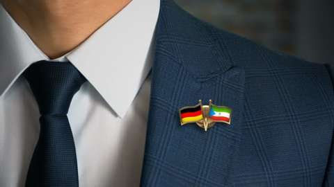 Businessman Walking Towards Camera With Friend Country Flags Pin Germany - Equatorial Guinea