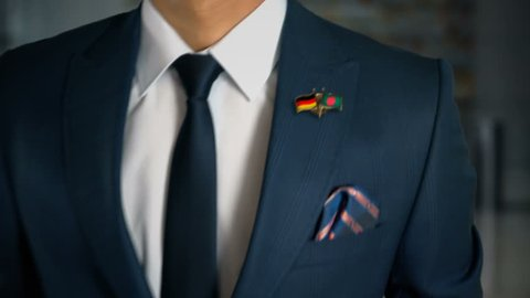 Businessman Walking Towards Camera With Friend Country Flags Pin Germany - Bangladesh