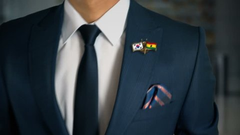 Businessman Walking Towards Camera With Friend Country Flags Pin South Korea - Ghana