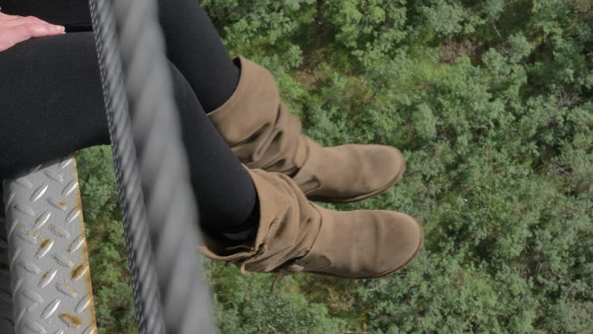 The legs of a young woman hanging and swinging relaxed very high over a river landscape. The person is clearly enjoying the moment. | Shutterstock HD Video #1015416196