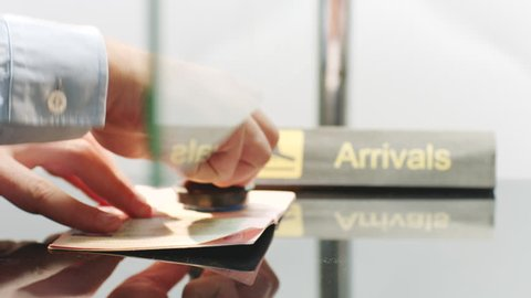 Customs officer stamping a travelling passport at arrivals