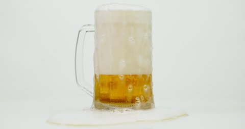 Pouring mug of beer with foam running out isolated on white background rotating. Overflowing beer glass