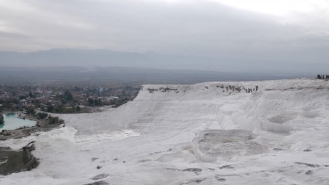 Panning shot of travertine terraces in Pamukkale with distant view of the town, Turkey
