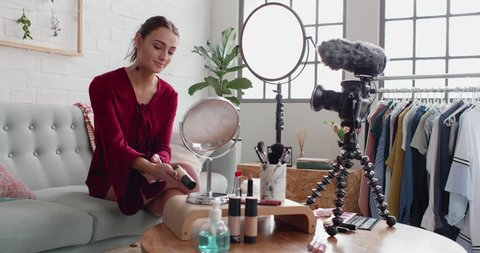 Female beauty vlogger recording a make-up tutorial demonstrating showing cosmetic product, modern entrepreneur
