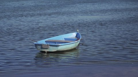 Small blue fishing boat on water
