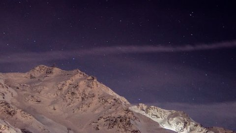 4K time lapse video of ta day to night sky with a snow-covered mountain and the cablecar station on top of it. In Val Thorens ski resort, in the Franch Alps.