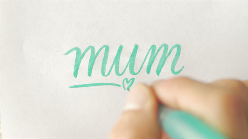 Handwriting the word MUM in cursive and a heart underneath on white paper with a green brush ink pen