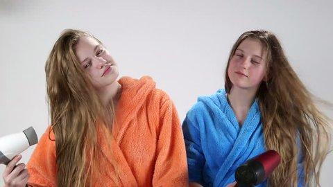 Teenage girls drying long hair after bath with hair dryer