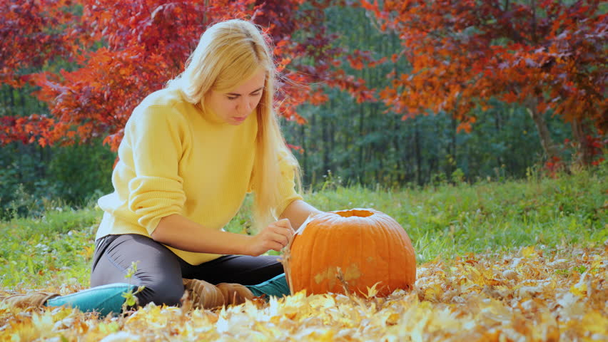 Young woman carves a pumpkin. Sitting in the yard in the background of yellowing trees