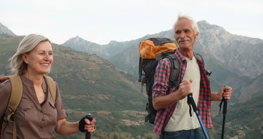 Positive mature caucasian couple trekking in mountains with backpacks, enjoying their adventure 4k #1015494796