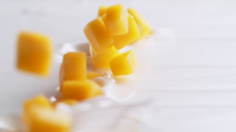 Tossing diced mango in yoghurt. Shot with high speed camera, 4K. Slow Motion.