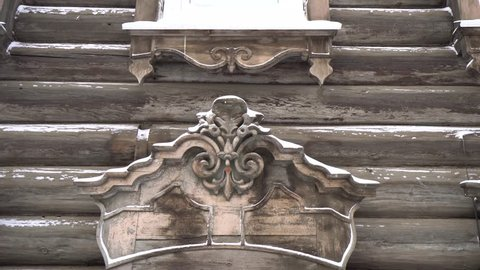 Cold Siberian winter wooden old house Steadicam close. Unique authentic Russian style wood carving architecture. Irkutsk center tourist attraction. White snow wind blizzard. Gimbal professional 4k