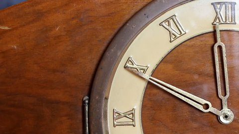 Close up of quarter of old wooden clock face. Minute hand moving fast and stops at 12 o'clock