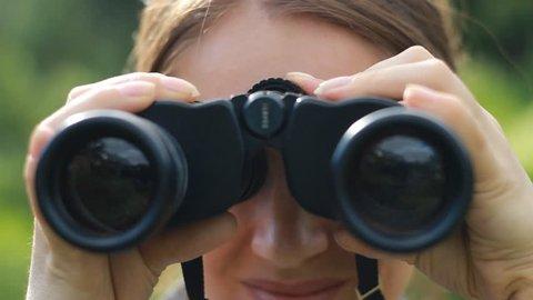 Woman tourist looking through binoculars closeup. Watch the object, spy.