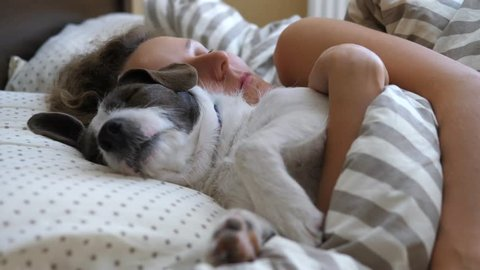 Young Woman Sleeping With Dog In Bed.