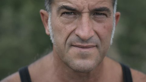 Portrait of handsome serious man with grizzled long sideburns and a black tank top looking at camera. Portrait of a middle aged biker.