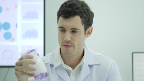 Portrait of Crazy and mad scientist looking and holding laboratory glass bottle with purple liquid.
