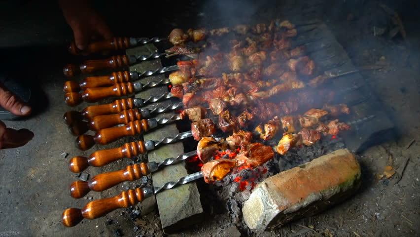 Marinated shashlik preparing on a barbecue grill over charcoal. Shashlik or Shish kebab popular in Eastern Europe. Shashlyk (skewered meat) was originally made of lamb. Roast Beef Kebabs On BBQ Grill