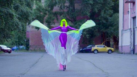 Girl on stilts in violet clothing dance on the street