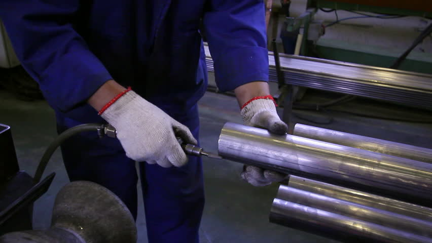 Hands working on the background of stainless steel pipes in factory. Metal-rolling machines for production rolled metal is used for manufacture of parts or an independent element. | Shutterstock HD Video #1015624726
