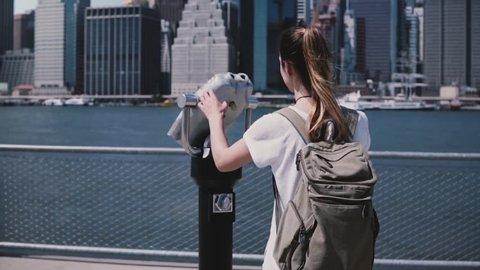 Young traveler girl looks through coin binocular telescope at amazing city skyline of Manhattan, New York slow motion.