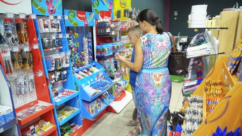 Vinnitsa, Ukraine - August, 2018: Back to school concept. Young mother and little boy buying school supplies in store