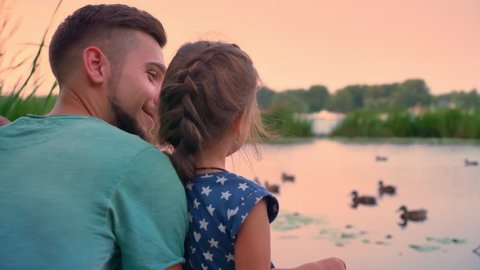 Handsome father is sitting with his small daughter near lake and watch ducks, talk, sunset, family concept