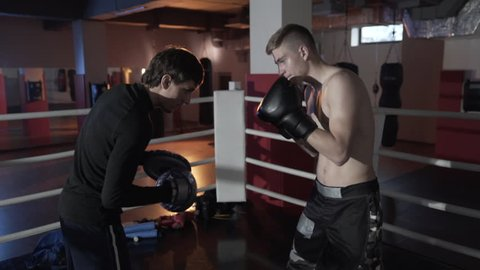 The young boxer reflects the attacks of his opponent. the coach deals with his charge in the ring, attacks and dodges attacks. Close-up side view. The concept of boxing, ring, boxing outfit.