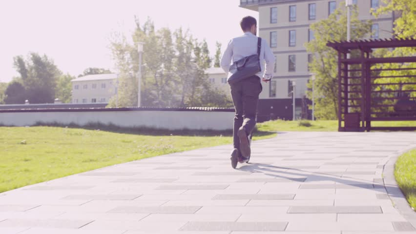 Dolly shot. A man in a business suit riding a kick scooter in a park then he taking scooter and going up stairs. Rear view