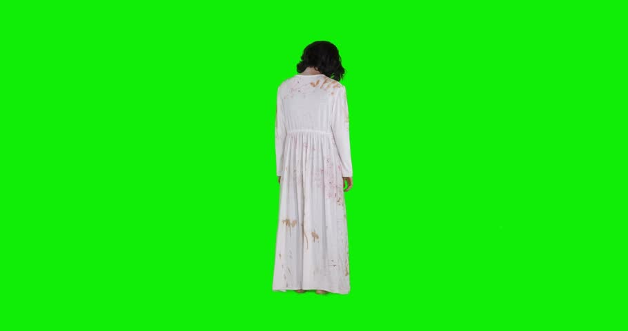 Creepy zombie woman with wounded face and white gown standing in the studio, shot in 4k resolution with green screen background