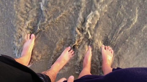 A couple in the swash zone of the beach with waves washing over their feet.