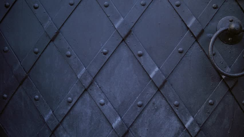 An old medieval restored black metal door reinforced with overlaid plates. Move the camera from top to bottom.